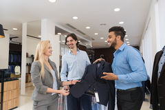 Handsome Business Man And Woman Fashion Shop, Customers Choosing Clothes In Retail Store. Young People Shopping Formal Wear Royalty Free Stock Photography