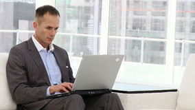 Handsome business man working at a laptop
