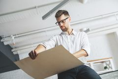 Handsome business man working on project. Handsome business man working on engineering or architectural project in modern bright office. Engineer, occupation and Royalty Free Stock Photo