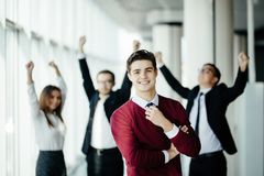 Handsome business man in front of his team member celebrating their achievement in office. Handsome business men in front of his team member celebrating their royalty free stock image