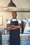 Handsome business owner stands by cafe counter. Lined with glass jars and a stainless steel coffee machine stock photo