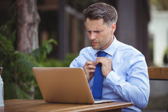 Handsome businessman adjusting tie while using laptop. At outdoor caf Stock Photos