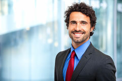 Handsome businessman against blurry background Stock Photo