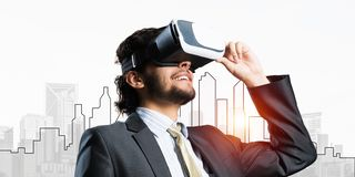 Handsome businessman against sunrise above city experiencing impressive virtual reality stock image