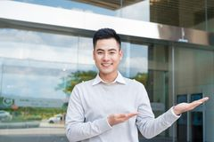 Handsome businessman with arm out in a welcoming gesture Stock Photo