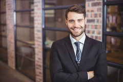 Handsome businessman with arms crossed standing in office Royalty Free Stock Photography