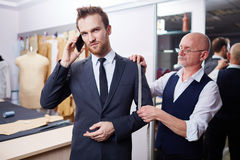 Handsome Businessman in Atelier Studio. Portrait of handsome men speaking by phone and looking at camera during model fitting of tailored suit in atelier Stock Photo