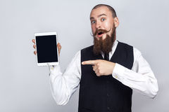 Handsome businessman with beard and handlebar mustache holding digital tablet and looking at camera and showing screen with finger. And surprised. studio shot stock images