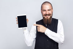 Handsome businessman with beard and handlebar mustache holding digital tablet and looking at camera and showing screen with finger. And laughing. studio shot stock image