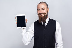 Handsome businessman with beard and handlebar mustache holding digital tablet and looking at camera and showing screen with smiley. Face. studio shot, on gray royalty free stock image