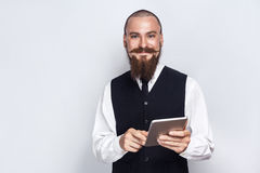 Handsome businessman with beard and handlebar mustache holding digital tablet and looking at camera with smiley face. Studio shot, on gray background stock images