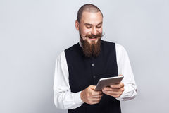 Handsome businessman with beard and handlebar mustache holding digital tablet looking at screen with toothy smile. Studio shot, on gray background royalty free stock photo