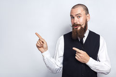 Handsome businessman with beard and handlebar mustache looking at camera, surprised and showing copy space with fingers. Studio shot, on gray background stock photography