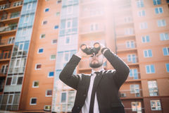 Handsome Businessman with binoculars spying on competitors outdoors. Handsome Businessman with binoculars spying on competitors Royalty Free Stock Images