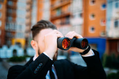 Handsome Businessman with binoculars spying on competitors outdoors. Handsome Businessman with binoculars spying on competitors Royalty Free Stock Image