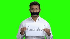 Handsome businessman with black tape on his mouth. Silenced man holding card with inscription Censorship. Alpha Channel background stock footage