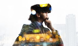 Handsome businessman in bokeh lights experiencing impressive virtual reality technology royalty free stock photography