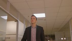 Handsome businessman in business suit walking in corridor business office. Cheerful manager walking at hall inside modern business office. Business people stock video footage