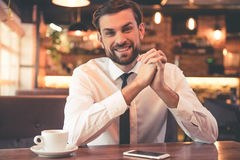 Handsome businessman in cafe. Handsome businessman is looking at camera and smiling while having coffee break in cafe Royalty Free Stock Photography