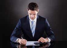 Handsome businessman calculating finance at desk Stock Images