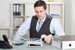 Handsome Businessman Calculating at his Worktable Royalty Free Stock Images