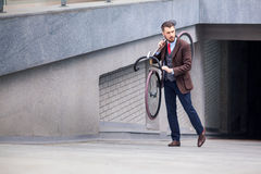 Handsome businessman carrying his bicycle Royalty Free Stock Images