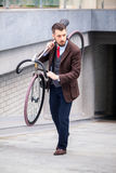 Handsome businessman carrying his bicycle Stock Images