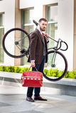 Handsome businessman carrying his bicycle in Royalty Free Stock Image