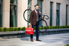 Handsome businessman carrying his bicycle in Stock Images