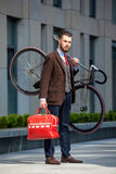 Handsome businessman carrying his bicycle Stock Photos