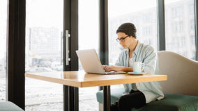 Handsome businessman in casual wear and eyeglasses is using a laptop in cafe Royalty Free Stock Photo