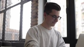 Handsome businessman in casual wear and eyeglasses is using a laptop in cafe. Young handsome businessman in casual wear and eyeglasses is using a laptop sitting stock video footage
