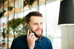 Handsome businessman in casual wear is talking on the mobile phone, gesturing while standing in the office Royalty Free Stock Images