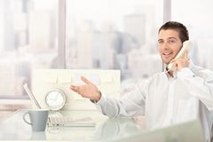 Handsome businessman chatting on phone. Handsome young businessman chatting on phone in bright office royalty free stock photo