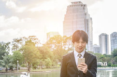 Handsome businessman checking emails on the phone. In city stock photos