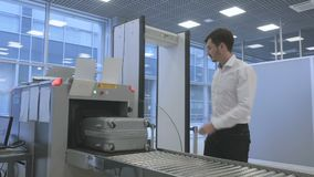 Handsome businessman checking luggage with x-ray scanner in the airport. Handsome businessman is in the security check room in the airport. Cute airport worker stock footage