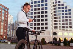 Handsome businessman in classic suit with bike is using a smart phone stock images