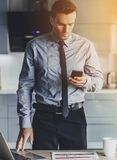Handsome Businessman in Classic Suit Using Phone. And Laptop While Standing in Modern Kitchen at Sweet Home. Businessman Passionate About Work. Guy Reading Stock Photography