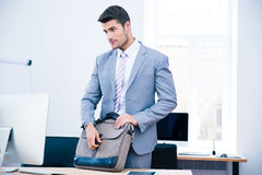 Handsome businessman closing bag on the table Stock Photography