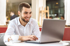 Handsome businessman on coffee break. Handsome businessman using laptop during coffee break in cafe Stock Images