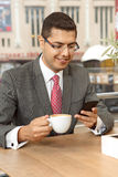 Handsome businessman on coffee break. Using smartphone Royalty Free Stock Images