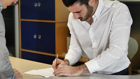 Businessmen signing contract or document. Handsome businessman at counter in his office, receiving document or contract and signing it with a pen, talking to stock footage