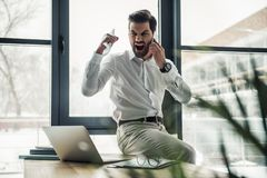 Handsome businessman working. Handsome businessman is crumpling paper and screaming while talking on the mobile phone in the office Stock Photo
