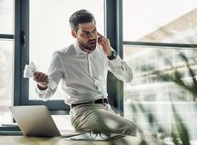 Handsome businessman working. Handsome businessman is crumpling paper while talking on the mobile phone in the office Stock Images