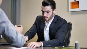 Businessmen signing contract or document. Handsome businessman at desk in his office, receiving document or contract and signing it with a pen, talking to client stock video footage