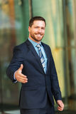 Handsome businessman doing handshake. Handsome young  businessman with beard and blue eyes giving a handshake Stock Photo