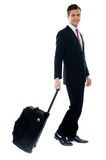 Handsome businessman dragging trolley bag. As he walks Royalty Free Stock Images