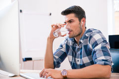 Handsome businessman drinking water in office Royalty Free Stock Photo