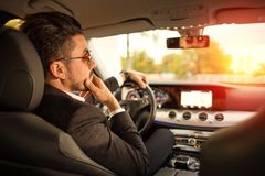 Handsome businessman driving car royalty free stock photos