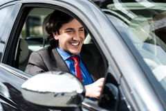 Handsome businessman driving a luxurious car Stock Photos
